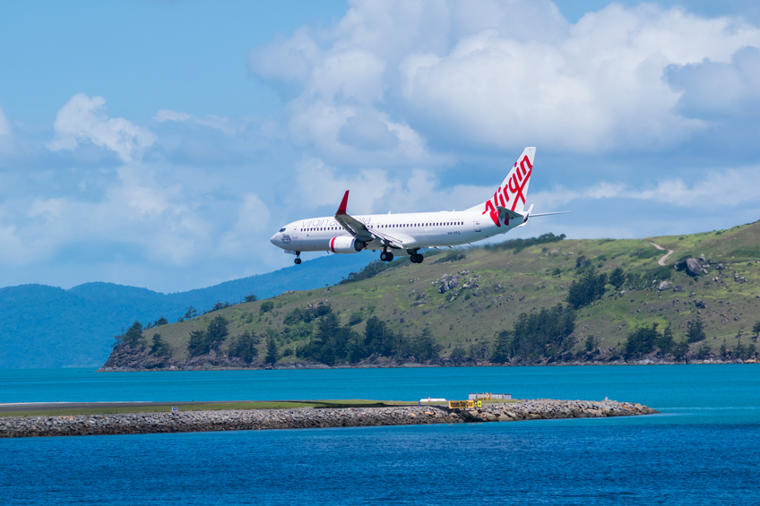 Hamilton island Australia, April 17-2014 Boeing 737-800 flying above the water is about to land on the runway on a beautiful day.
